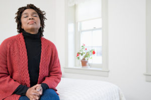 Woman sitting in bedroom with eyes closed