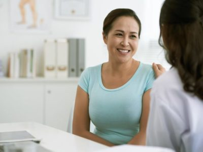 Seated woman smiling at healthcare provider